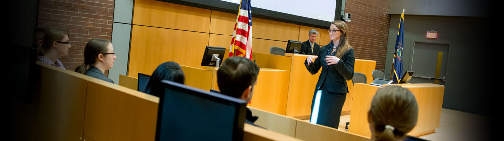 A Dickinson Law student addresses a jury, with a judge looking on from the bench, as part of mock trial exercises in a courtroom.