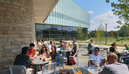 People sit at tables on a patio outside Lewis Katz Building, Penn State Law, University Park campus