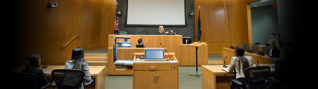 A judge talks with law students at Penn State University Park as part of mock trial exercises in a courtroom.