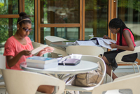 Two students study at tables in an atrium