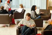 Students sit in armchairs in a study area, some with books, some with computers, some having conversations