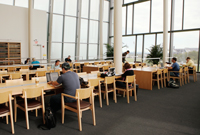 Students sit at study tables in a study area with many windows