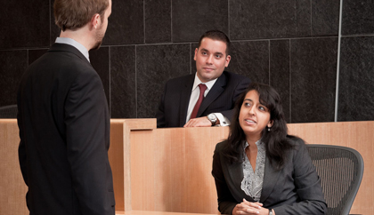 A woman sits in a witness chair in a courtroom as she talks with a lawyer standing near her. A man sits in the jury box nearby.