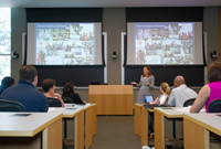 A professor lectures at the front of a full classroom that has side-by-side screens projecting images