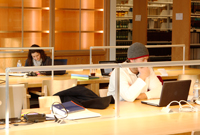 Two students study in the law library at tables with laptop computers